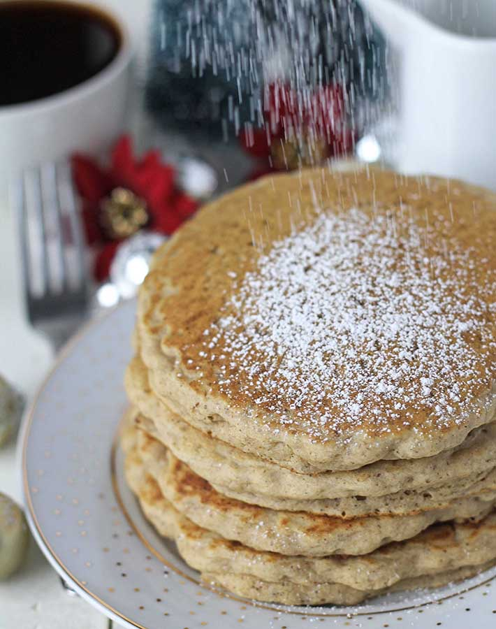 Powdered sugar being sifted on top of a plate of eggnog pancakes.