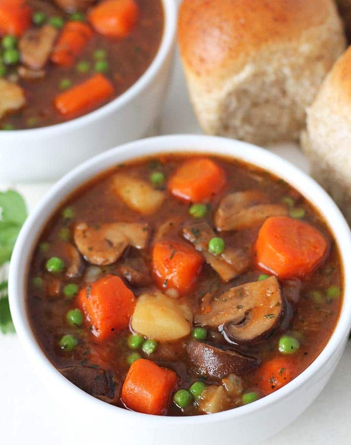 Two bowls of mushroom stew on a white table, a plate of whole wheat rolls sits in the background.