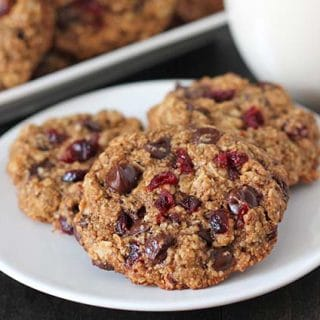 Three Oatmeal Cranberry Chocolate Chip Cookies on a plate, plate is on a wood table, glass of almond milk sits in the background.