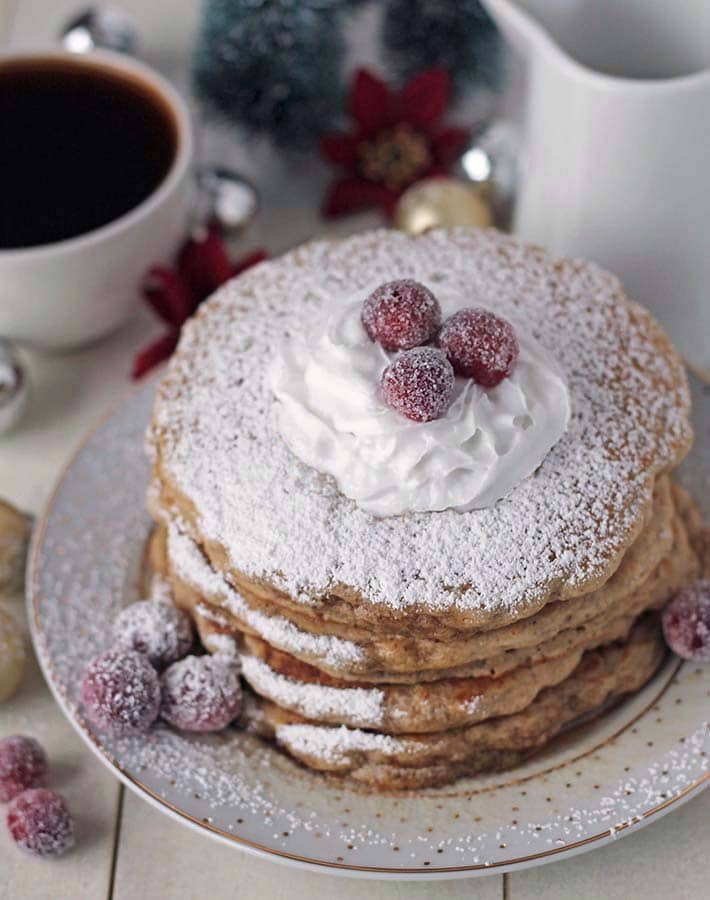 A stack of vegan eggnog pancakes on a plate.