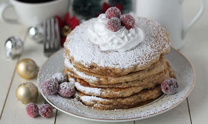 A stack of four vegan eggnog pancakes on a plate, pancakes are topped with coconut whipped cream and sugared cranberries.
