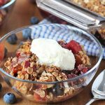 Vegan Peach Blueberry Crisp in a bowl topped with a small scoop of ice cream.