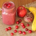 Cranberry Apple Smoothie in a mason jar mug on a burlap placemat with smoothie ingredients to the right.