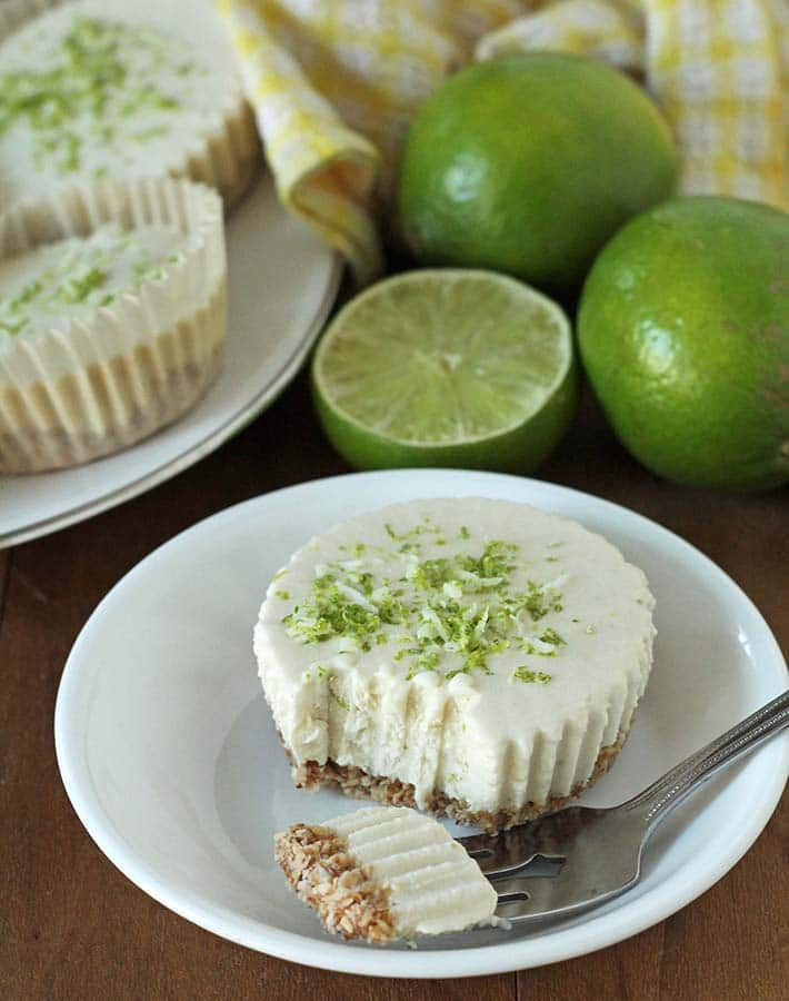 Vegan Lime Cheesecake on a plate witha piece taken out of it, piece is on a fork that also sits on the plate.