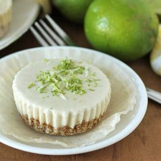 Vegan Lime Cheesecake on a plate, plate sits on a brown wooden table.