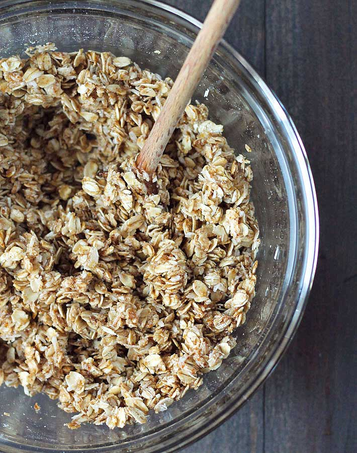 Mixture for nut free granola in a glass bowl with a wooden spoon.