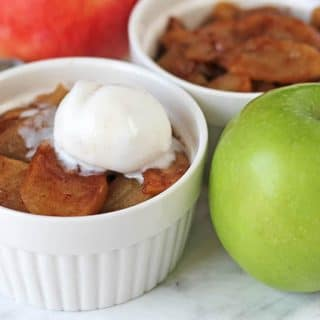 A small white bowl with baked cinnamon apple slices topped with ice cream, a green apple sits to the right of the bowl.