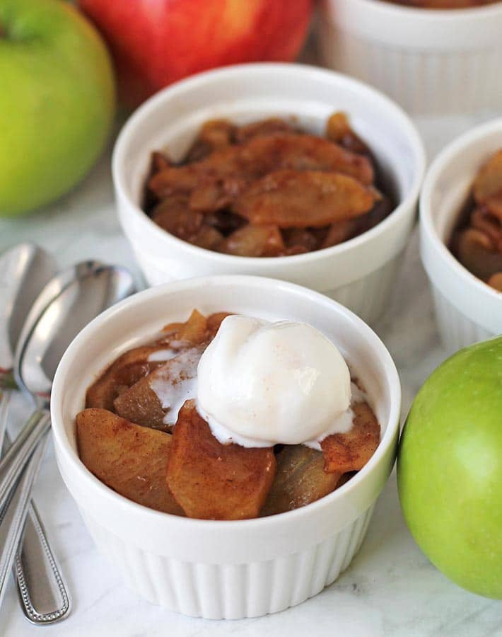 A remekin with baked cinnamon apple slices topped with a small scoop of coconut ice cream.