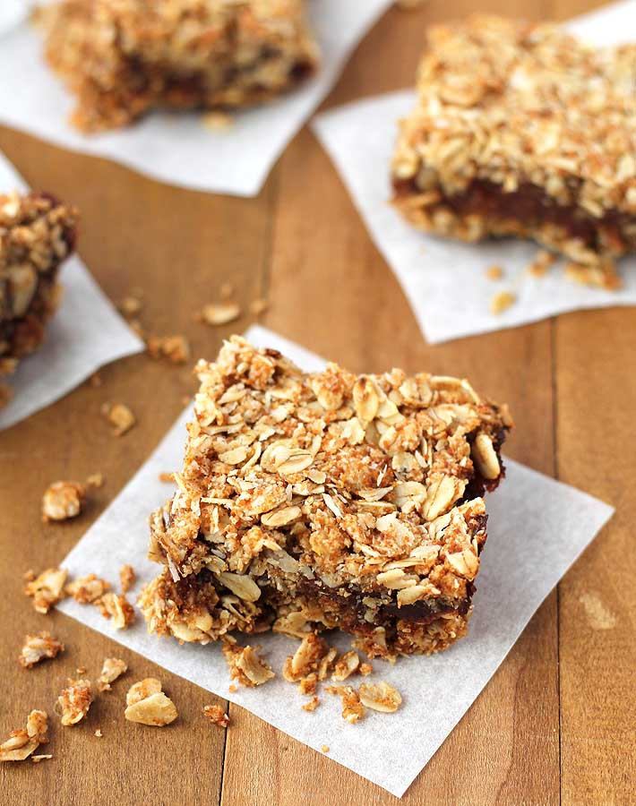Four vegan date squares on a brown table.