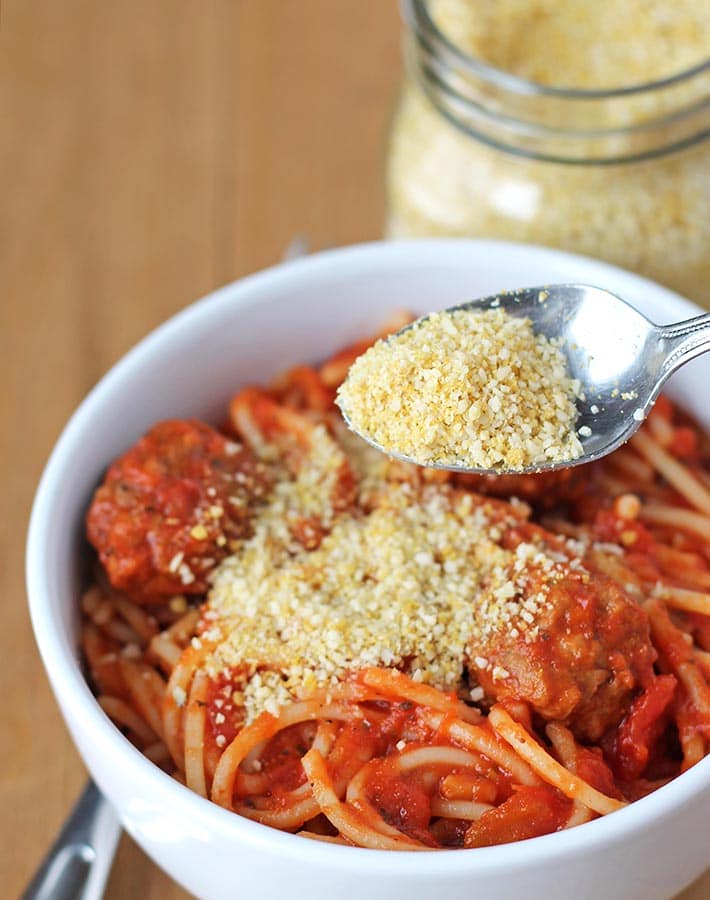 Vegan parmesan being sprinkled from a spoon onto a bowl of spaghetti.