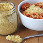 Vegan Parmesan in a spoon on a wood table, a jar of it sits in the background as well as a bowl of spaghetti.