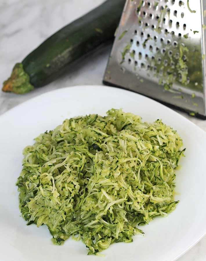 Shredded zucchini on a white plate to be used to make Gluten-Free Banana Zucchini Bread.