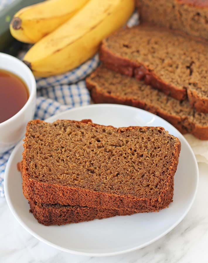 Two pieces of Gluten-Free Banana Zucchini Bread on a white plate, the rest of the loaf sits behind the plate.