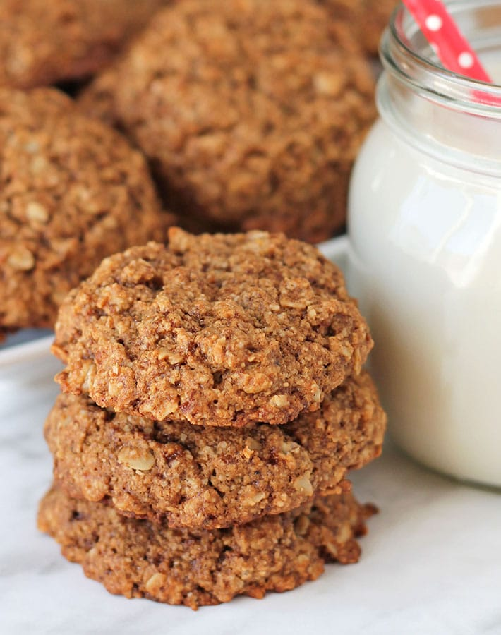 A stack of three Vegan Gluten Free Oatmeal Cookies sitting on a marble surface, a glass of milk sits to the right.