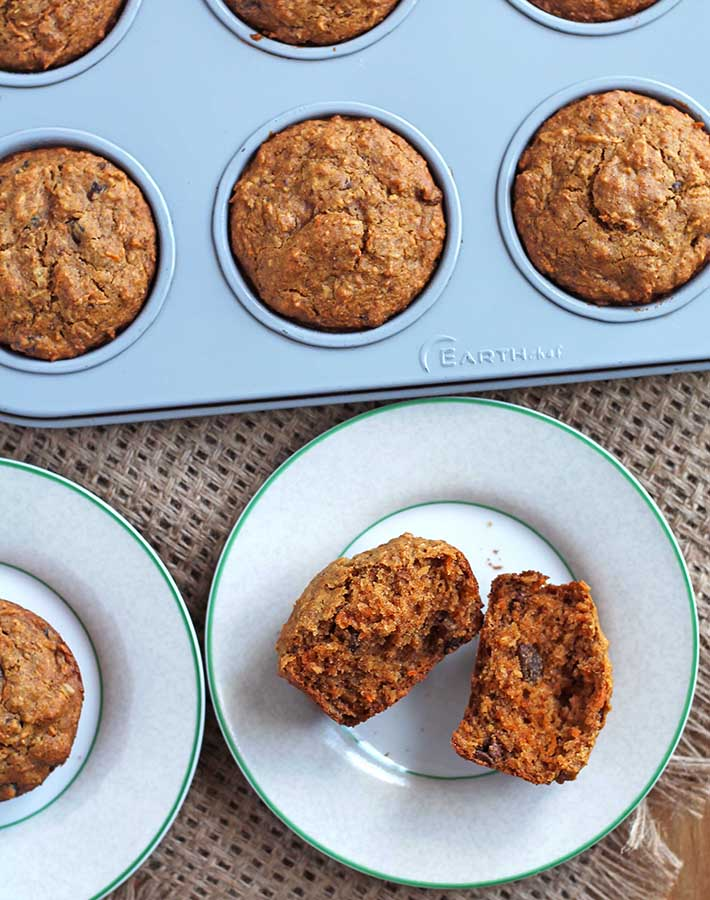 Carrot coconut muffins on a table, one is split and on a plate to show the inner texture.