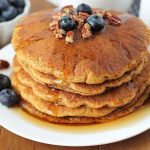 Four Gluten Free Sweet Potato Pancakes on a white plate garnished with fresh blueberries and pecans.