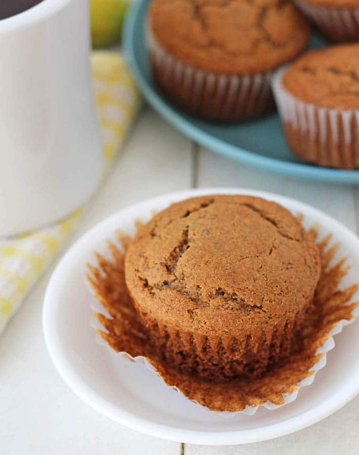 Vegan Gluten Free Banana Muffins on a blue plate, one muffin sits in front on a white plate.