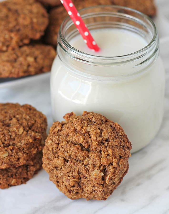 A Vegan Gluten Free Oatmeal Cookie leaning agains a glass of almond milk.