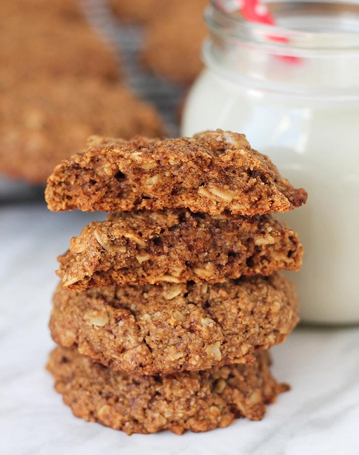 A stack of three Vegan Gluten Free Oatmeal Cookies, the top cookie is split in two to show the inner texture.