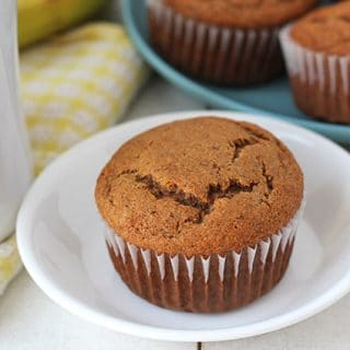 Vegan Gluten Free Banana Muffins on a white table, a cup of tea sits to the left.