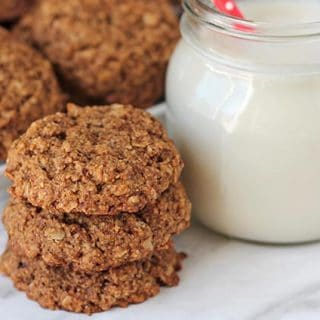 Vegan Gluten Free Oatmeal Cookies on a white surface with a glass of milk to the side.
