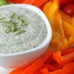 Close up shot of vegan veggie dip in a bowl with fresh vegetables around it.