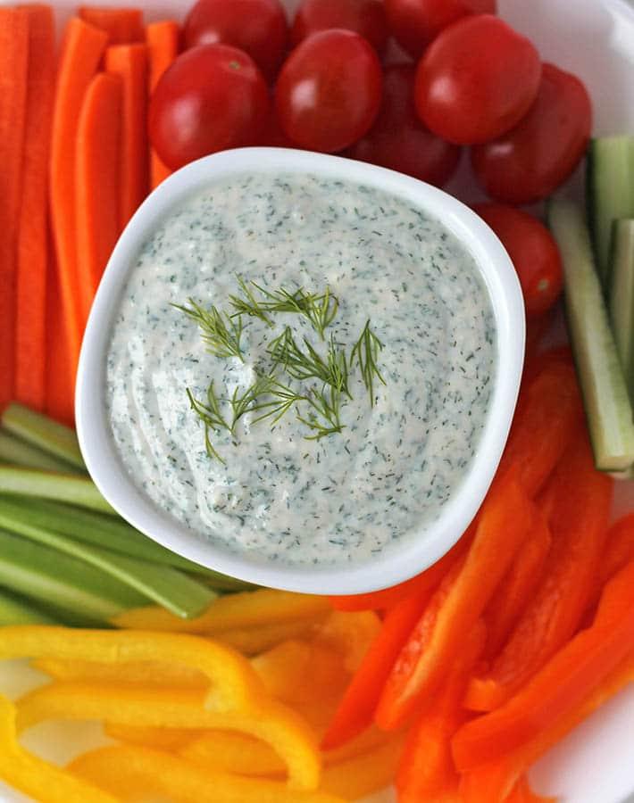 Vegan veggie dip in a bowl, fresh vegetables are around the bowl.