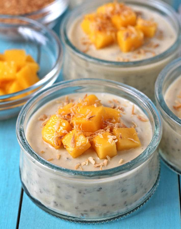 A cup of mango coconut chia pudding topped with fresh mango cubes and toasted coconut.