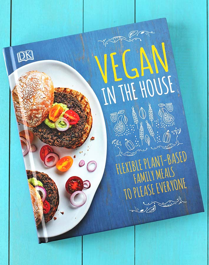 A copy of the cookbook Vegan in the House on a blue table.
