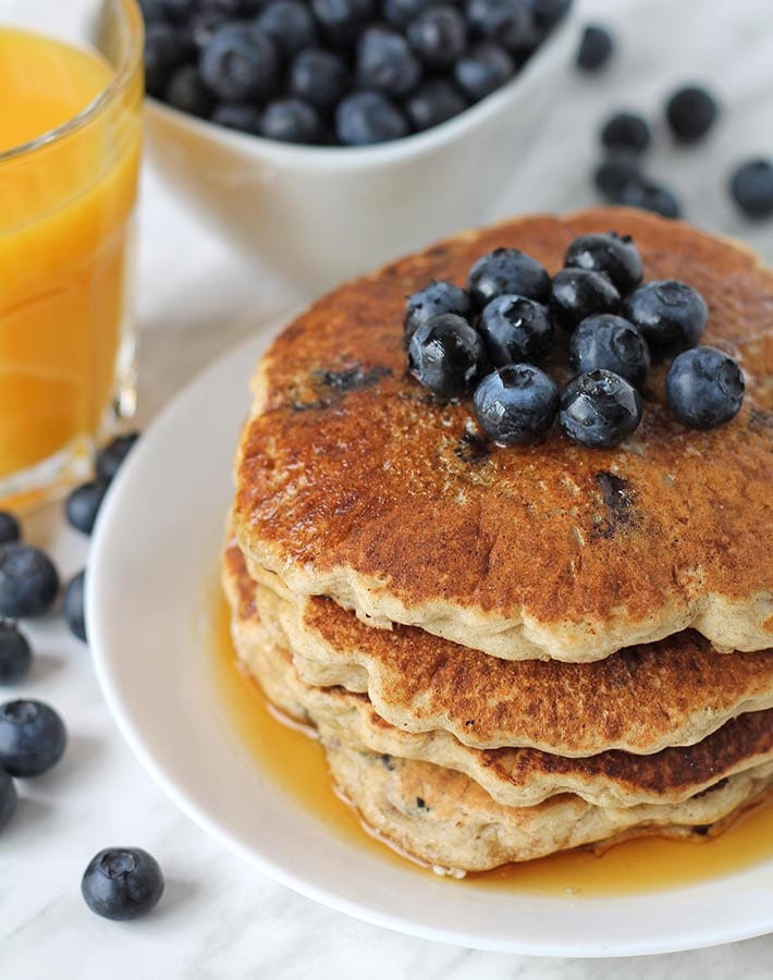 A stack of egg free blueberry pancakes on a plate.