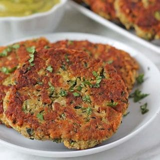 Three fried zucchini fritters ona plate, fritters are garnished with chopped parsley.