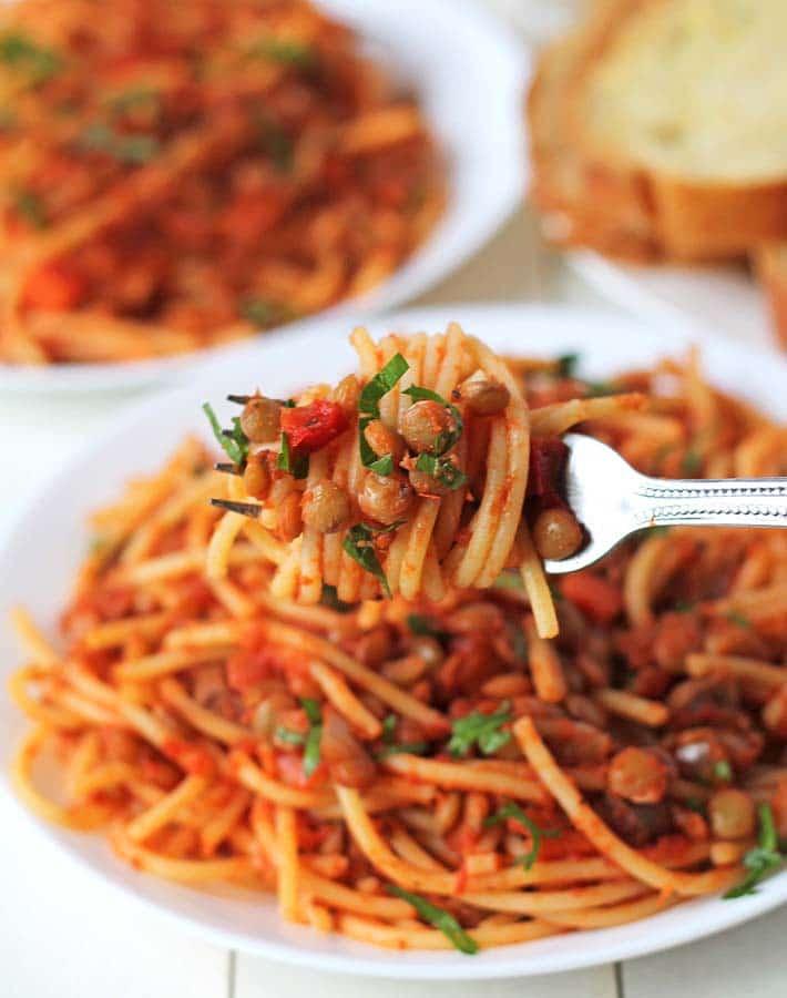 Green lentil pasta on a fork.