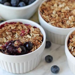 Three bowls of blueberry crisp with oatmeal on a marble surface.