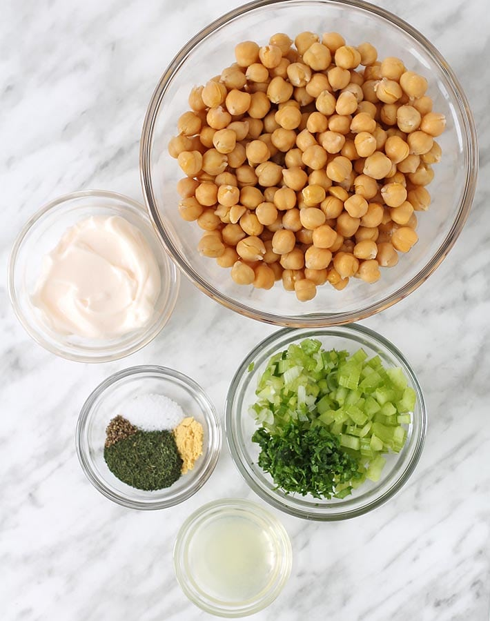 The ingredients for mashed chickpea salad in separate glass bowls, bowls are sitting on a white marble surface.