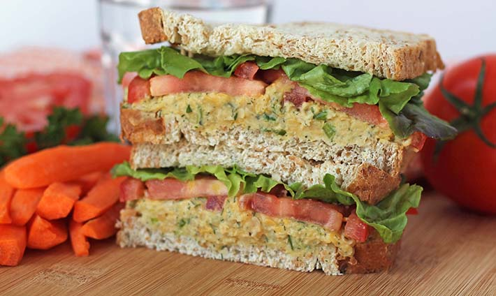 A close up shot of two halves of a vegan chickpea sandwich stacked on top of each other.