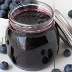 Small glass jar filled with vegan blueberry compote, jar is on a white table with fresh blueberries surrounding it.