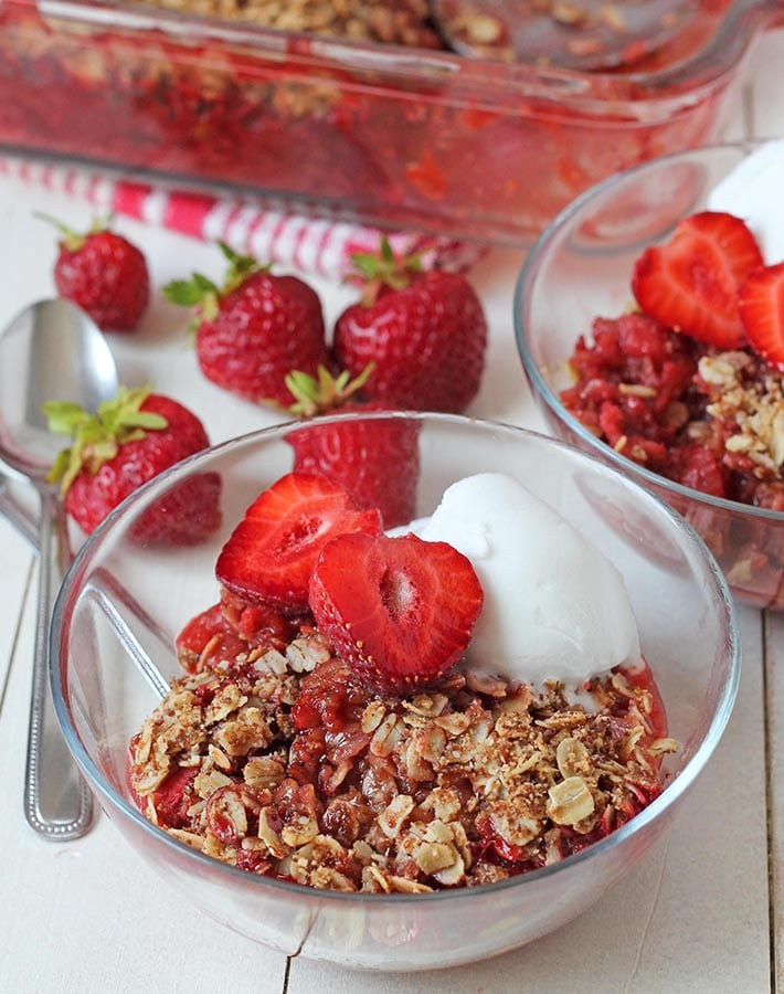 Rhubarb and strawberry crisp in a small glass bowl garnished with ice cream and fresh strawberries.