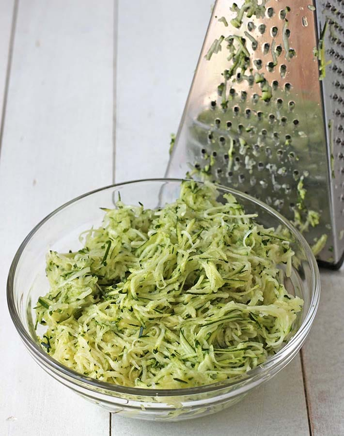 Shredded zucchini in a bowl with a greater behind the bowl.