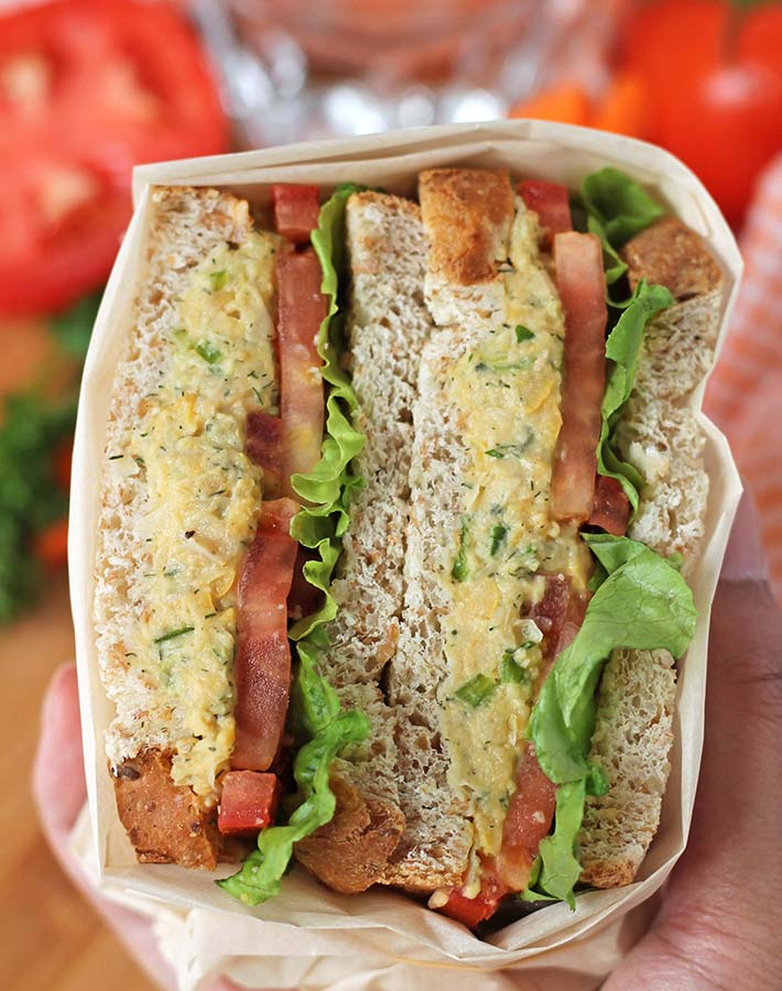 A hand holding a chickpea salad sandwich.