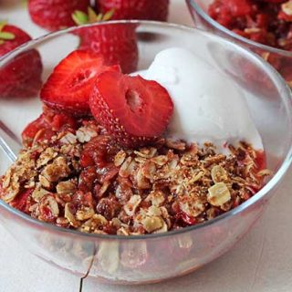 Gluten Free Strawberry Rhubarb Crisp in a small glass bowl on a white table.
