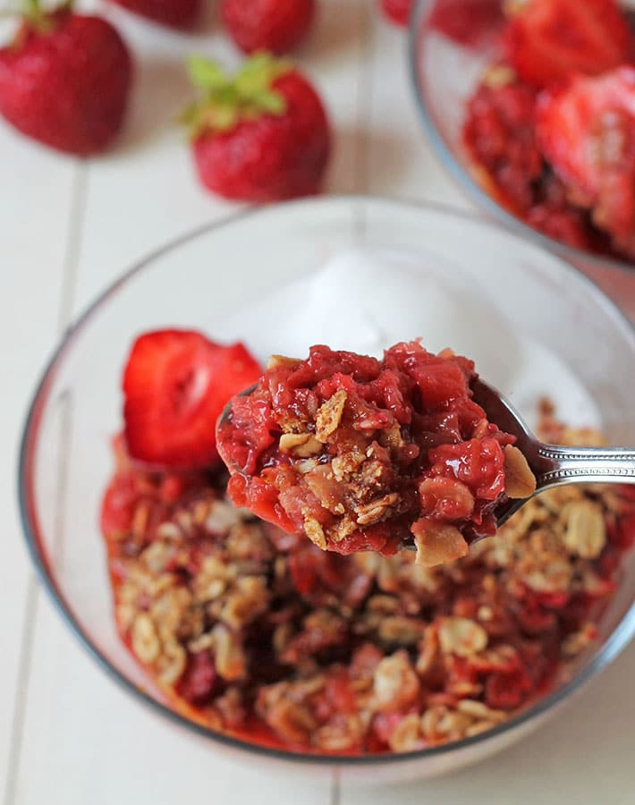 A close up shot of gf strawberry rhubarb crisp on a spoon.
