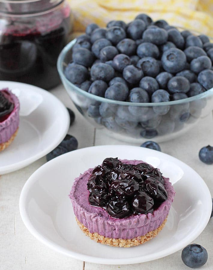 Mini vegan blueberry cheesecake topped with blueberry compote on a plate.