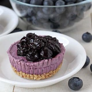 Close up shot of a vegan mini cheesecake topped with blueberry sauce on a small white plate.