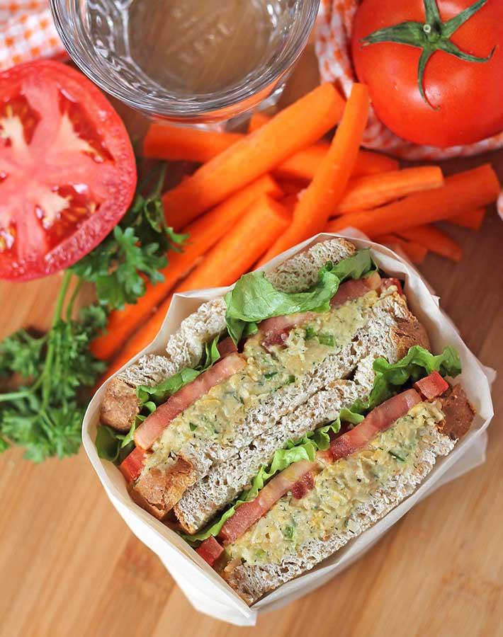 An overhead shot of a chickpea chicken salad sandwich on a bamboo cutting board, fresh vegetables surround the sandwich.