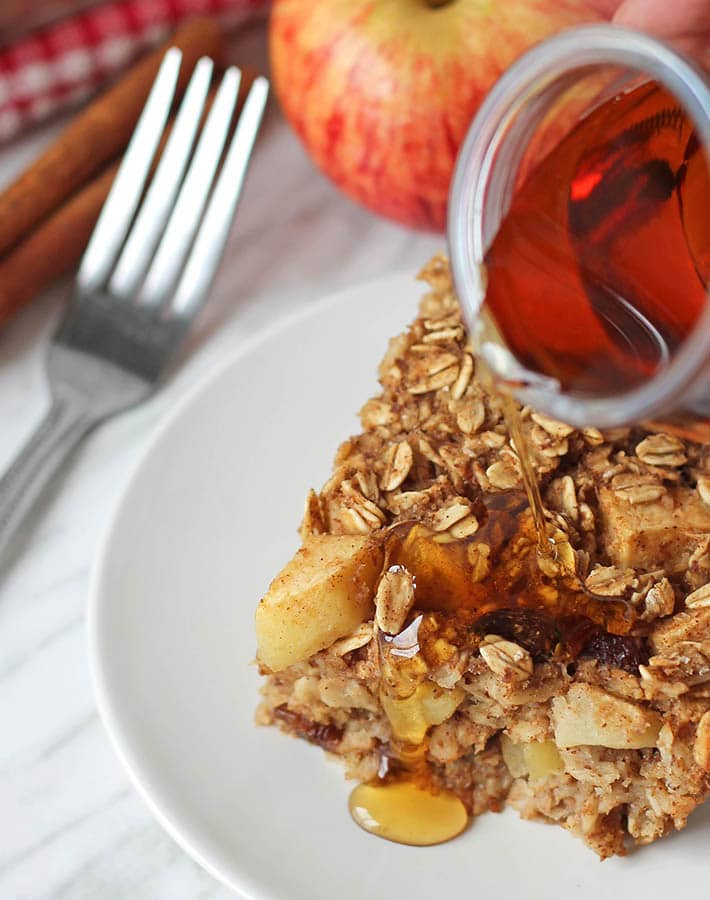 Maple syrup being poured onto a piece of vegan baked oatmeal.