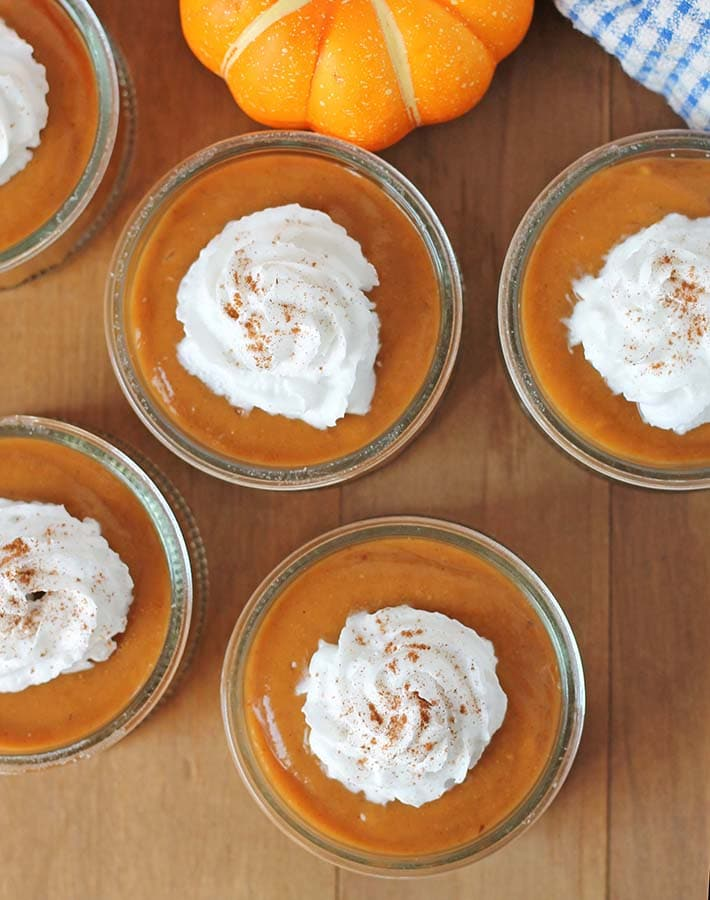 Overhead shot of dairy free pumpkin pie pudding cups sitting on a brown wood table.