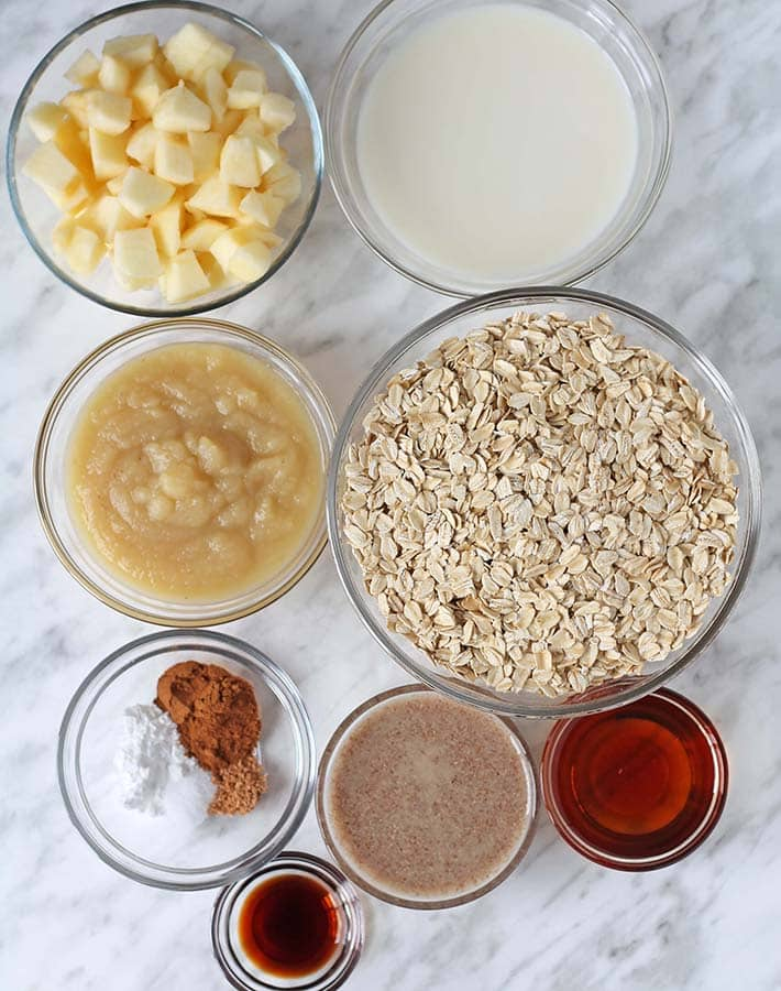 The ingredients for apple cinnamon baked oatmeal in separate glass bowls.