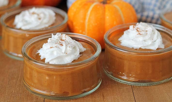 Vegan pumpkin pudding in glass serving jars sitting on a table, each pudding is topped with coconut cream.