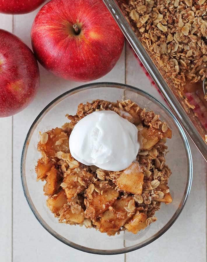 Overhead shot of vegan apple crisp in a small bowl, crisp is topped with a scoop of ice cream.