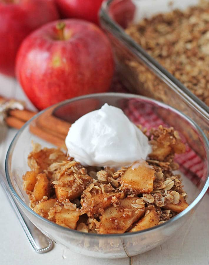Non dairy apple crisp in a small glass bowl with a scoop of coconut ice cream on top.